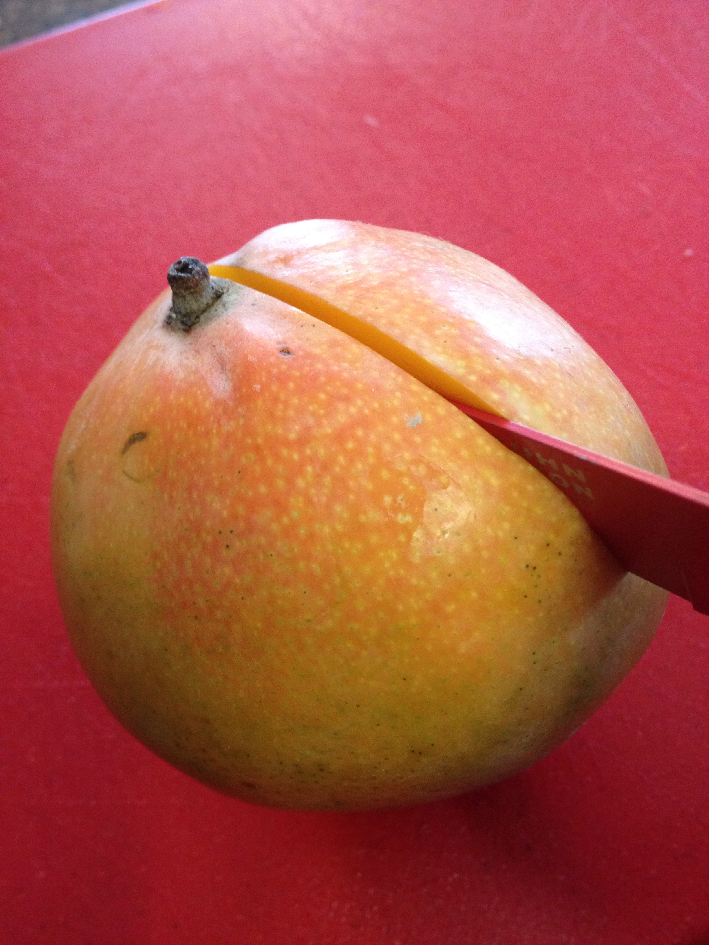 "Using The Stem As A Guide For Where The Pit Is, Cut Off One €�cheek"" Of The  Mango (follow The Hard Pit"